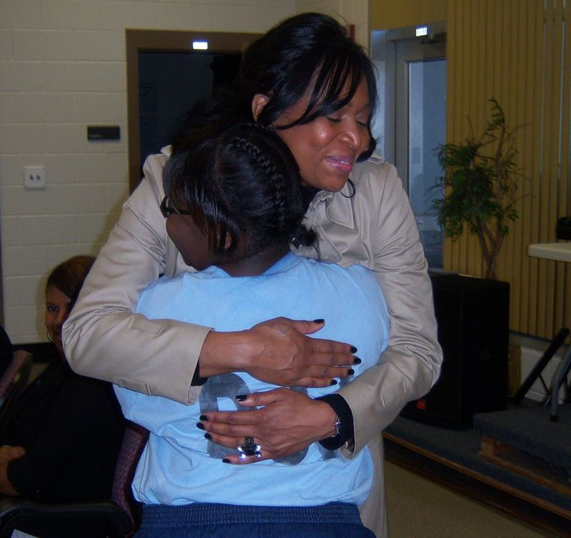 Marlo Hampton embracing a young girl at an Atlanta youth Detension Center final